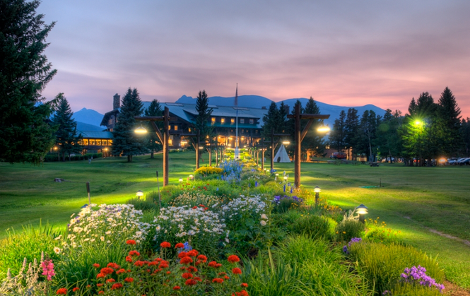 The St. Marys Inn at Glacier National Park with a beautiful flower garden at sunset